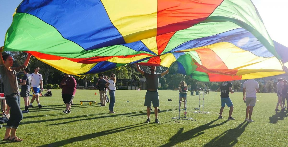 Students standing under a multi-colored parachute